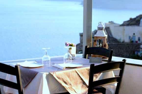 mesa e cadeiras a beira mar no restaurante Floga em Santorini nas ilhas gregas