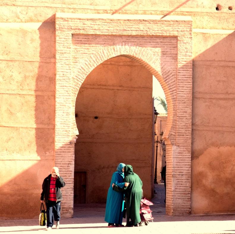 Mulheres se abraçando, com roupas tradicionais na Medina em Marrakech Marrocos