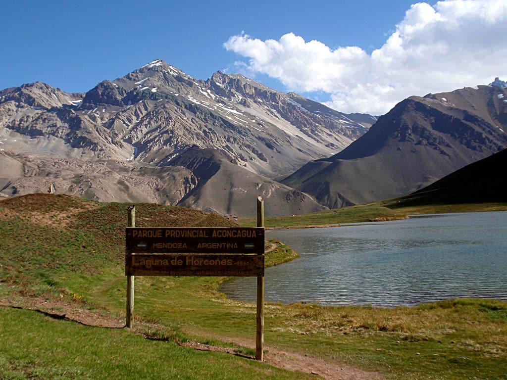 Placa anunciando o Parque Provincial do Aconcágua, com as montanhas ao fundo. Foto de Shlomi Yosef via Flickr.