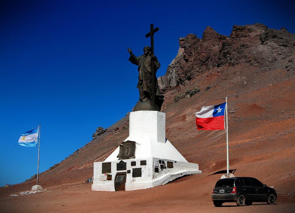 Monumento Cristo Redentor de Los Andes, próximo à fronteira, com as bandeiras da Argentina e do Chile, respectivamente. Foto de Diego Del Rio.