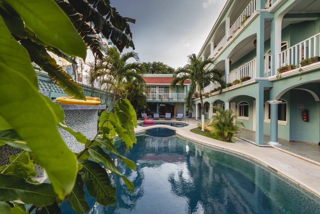 Vista das piscina do Selina Playa Del Carmen - piscina azul escura com folhagens e ao fundo o hotel