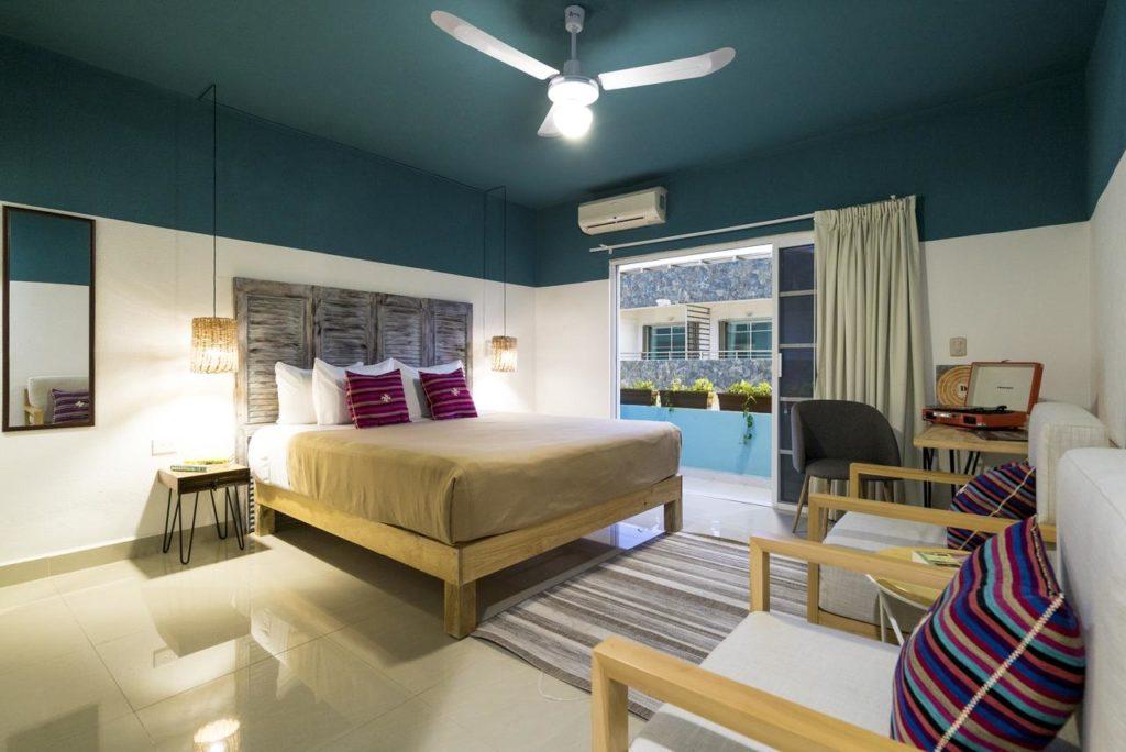 Quarto de casal do Selina Playa Del Carmen - cama de casal grande com travesseiros e almofadas roxas e decoraçao em tons azul e branco