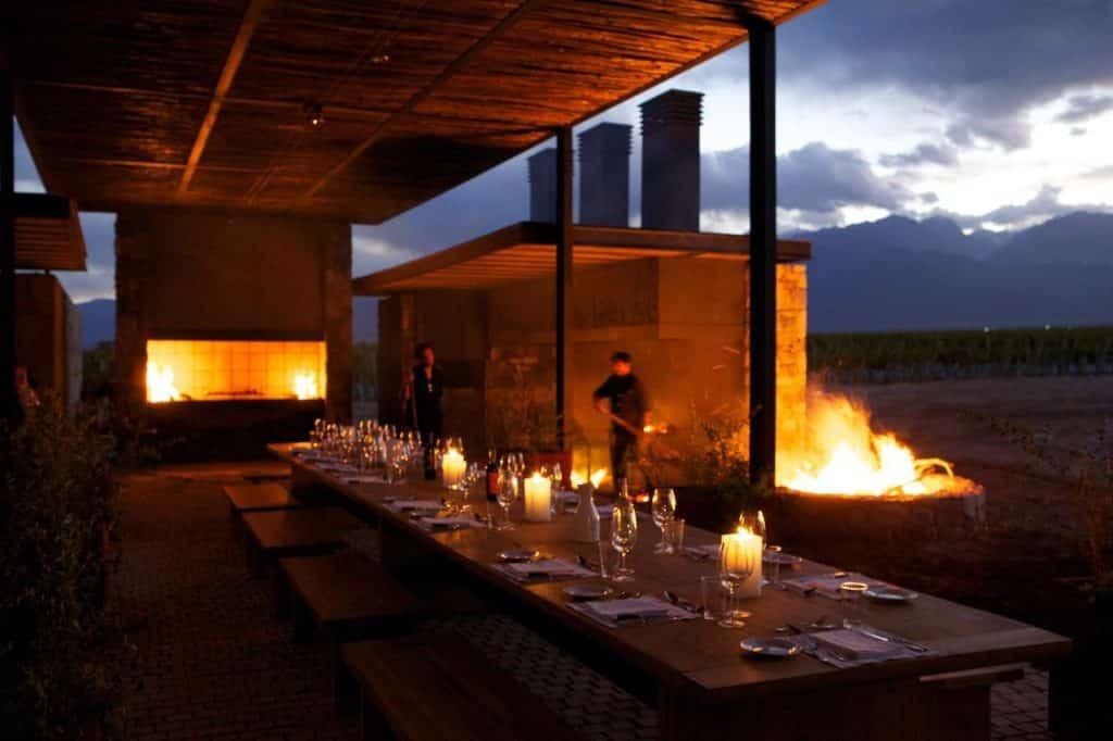 Mesa posta com forno aceso ao fundo, no luxuoso restaurante Siete Fuegos em Mendoza.