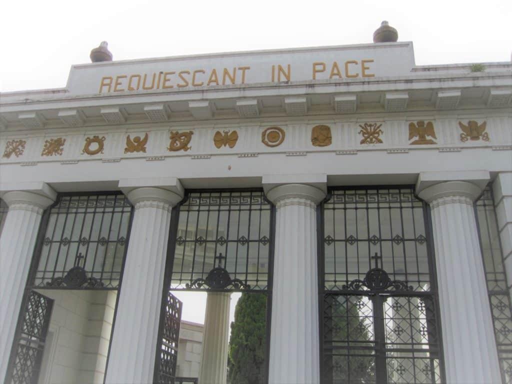 """Portão de entradas do cemitério da Recoleta em Buenos Aires. Colunas brancas, com portal preto e escrito ˜resquiescant in pace""""com letras douradas"""