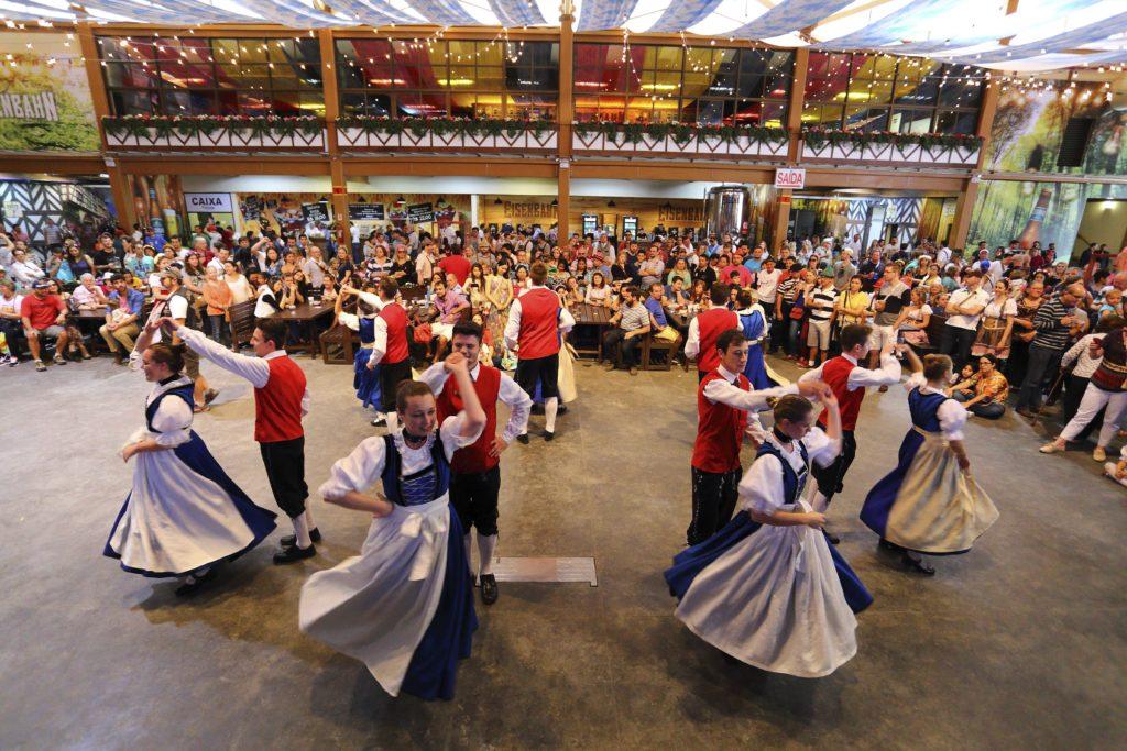 Casais caracterizados com roupas típicas alemãs dançando na Oktoberfest Blumenau. Foto do site oficial: http://oktoberfestblumenau.com.br