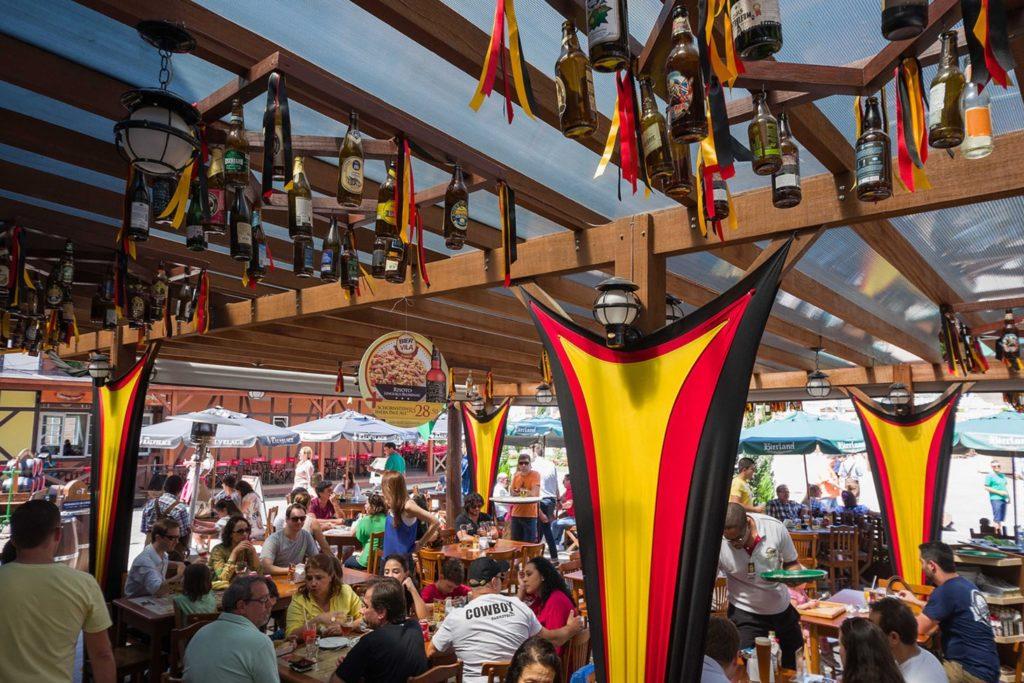 Espaço do restaurante Bier Vila em Blumenau, com bandeiras das cores da Alemanha (preto, vermelho e amarelo). Foto do site oficial Bier Vila.