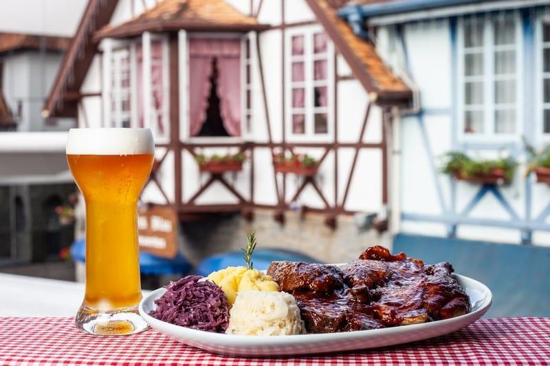 Taça de cerveja cheia e prato de marreco no restaurante Bier Vila. Foto do site oficial do restaurante.