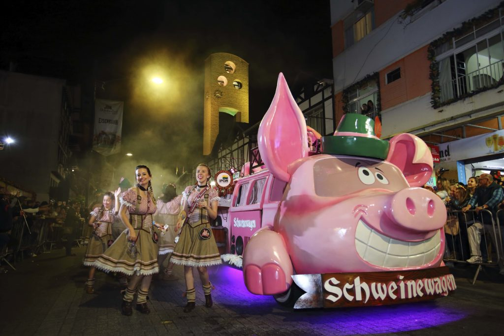 Parte do desfile da Oktoberfest Blumenau com duas moças caracterizadas em trajes típicos, e carro alegórico de porco ao lado. Foto do site oficial do evento: http://oktoberfestblumenau.com.br
