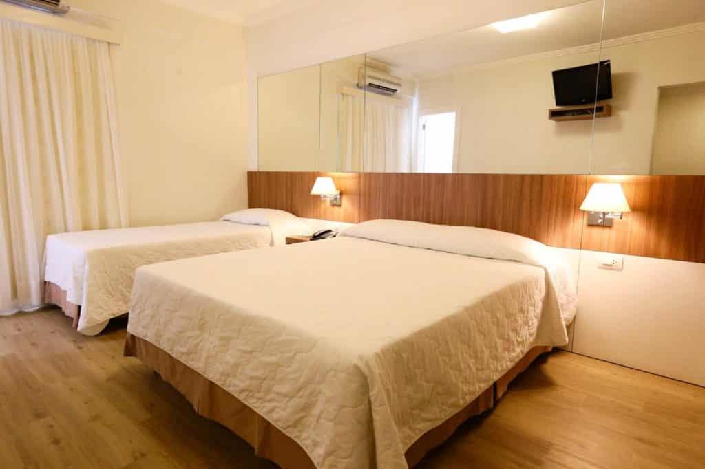Quarto com duas camas, solteiro e casal, no Hotel Glória em Blumenau. Foto de booking.com