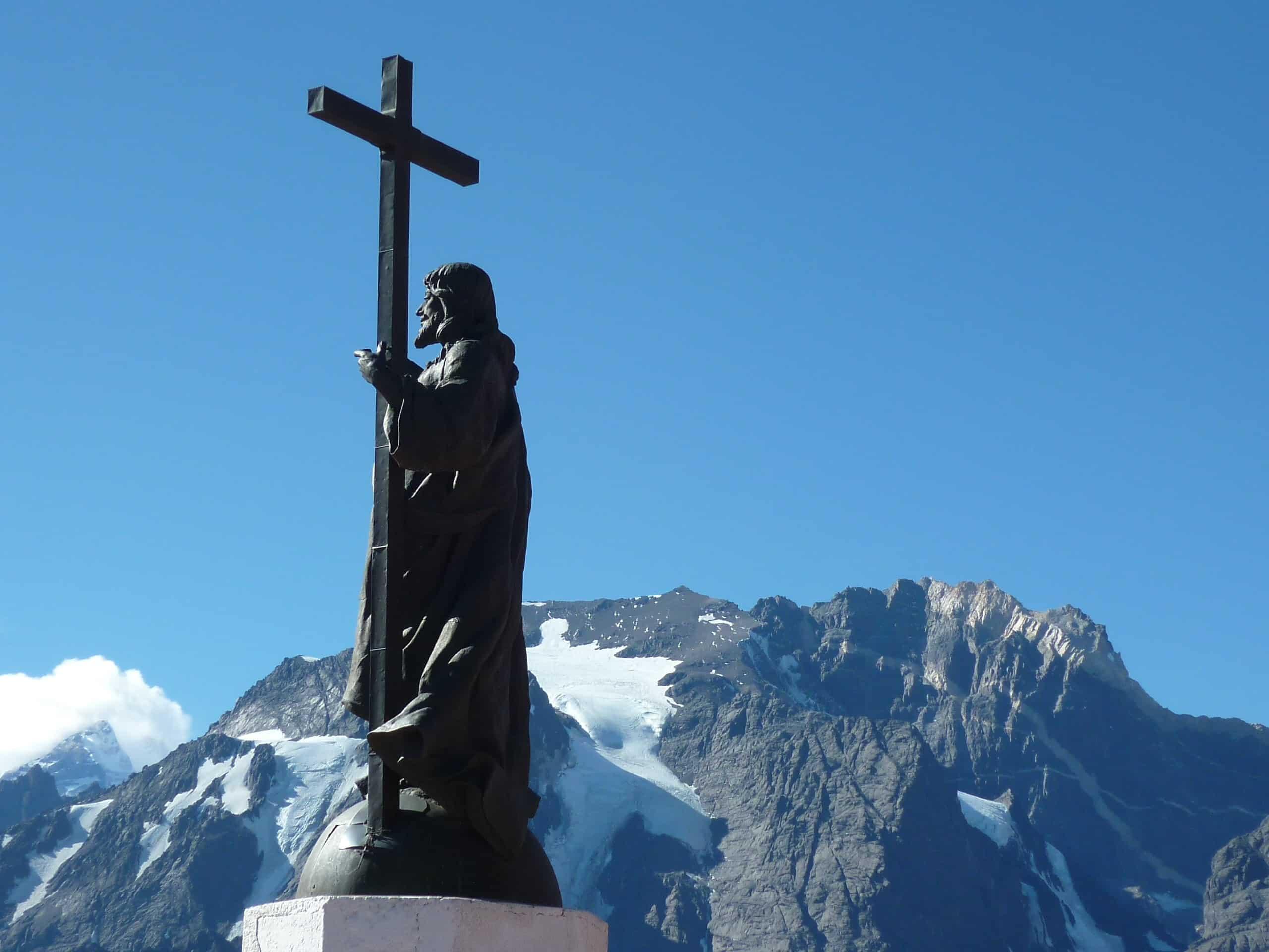 A imagem do Cristo Redentor de los Andes com montanhas ao fundo. Foto de KIAIMAR13 via Wikimedia.