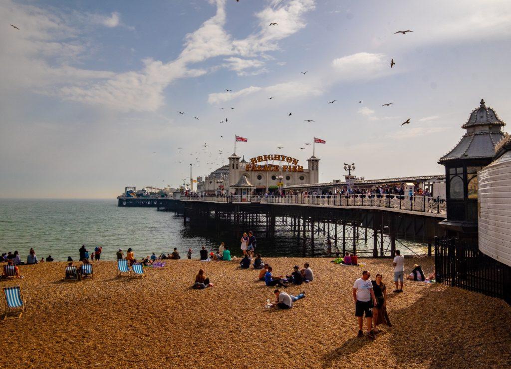 Pessoas curtindo dia ensolarado em praia do pier em Brighton. Foto de Ben Guerin on Unsplash.