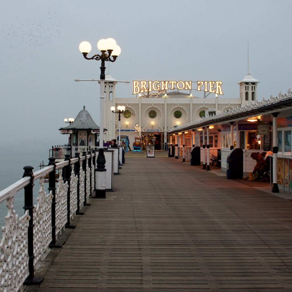 Vista da entrada do Brighton Pier com food trucks de venda de alimentos típicos ingleses. Foto de Paul Hudson via Flickr.