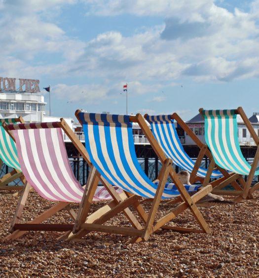 Vista de praia em Brighton com cadeiras e pier ao fundo. Foto de Willi Heidelbach via Pixabay.