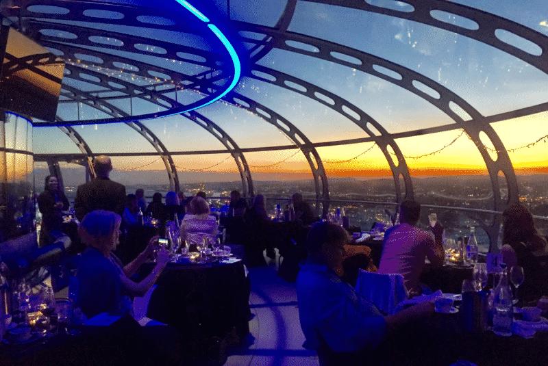 Pessoas jantando no topo do British Airways i360, com vista panorâmica para a cidade de Brighton, na Inglaterra. Foto de @BritishAirways via Facebook.