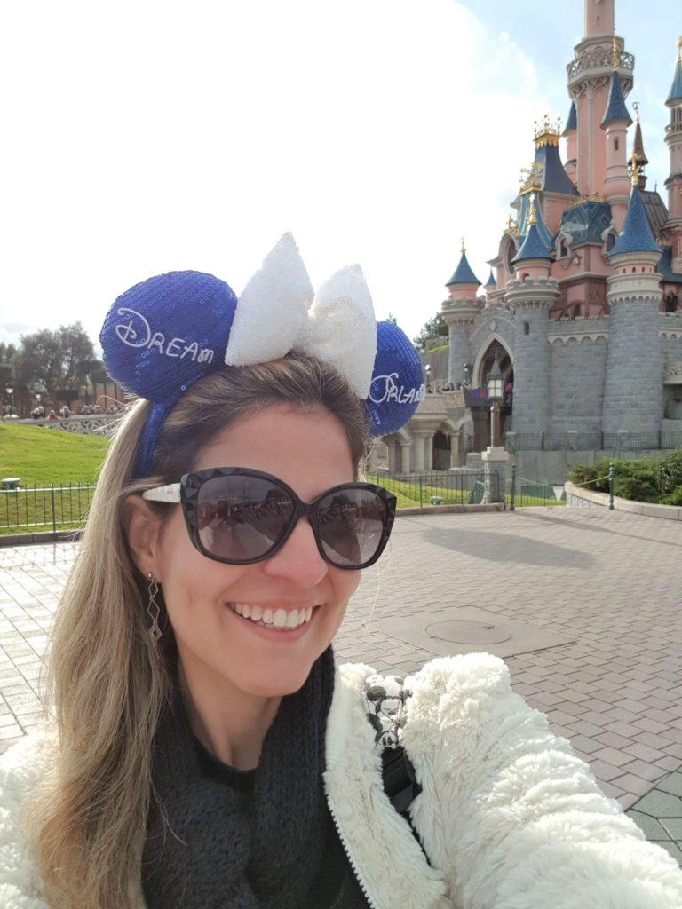 Isis Pacheco (autora do post) em foto com o castelo da Bela Adormecida da Disneyland Paris Parc ao fundo.