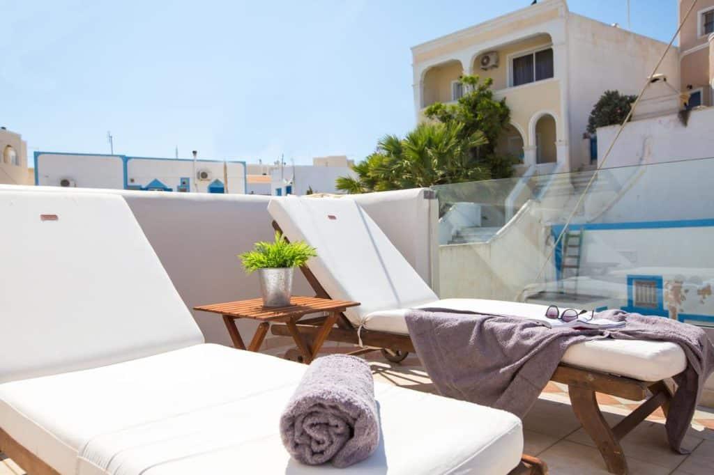 Espreguiçadeiras ao sol no hotel Aldea em Santorini.