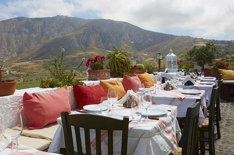 Vista de restaurante com mesinhas em varanda com vista para o mar, em Santorini.