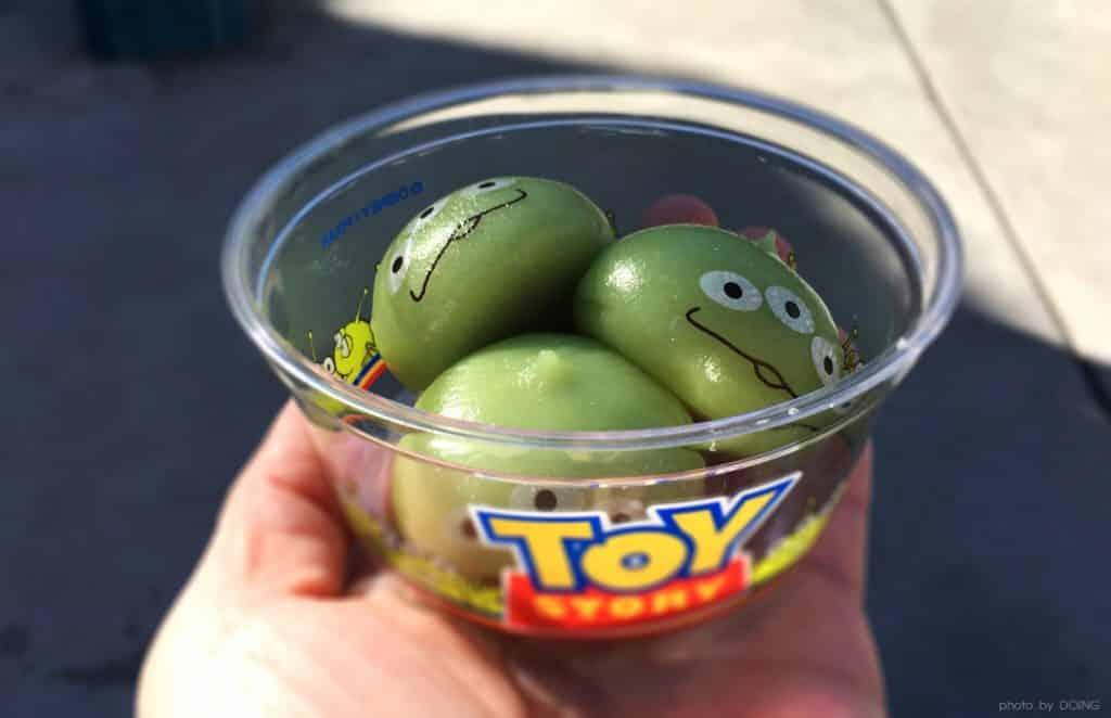 Mão segurando potinho de Toy Story com três unidades do bolinho mochi em formado de alien. Foto de Doing via Flickr.