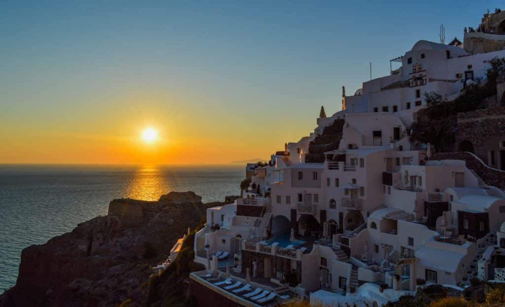 Vista da costa de Oia, em Santorini, com o Sol se pondo ao fundo. Foto de Gotta Be Worth It from Pexels.