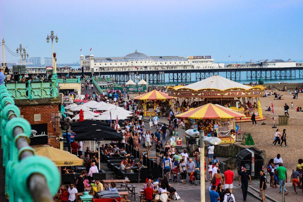 Parque de diversões e pier de Brighton próximo à orla da praia. Foto de Tom Wheatley via Unsplash.
