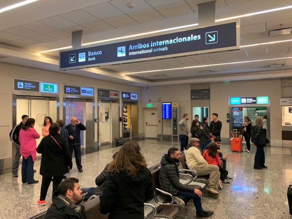 Vista de pessoas esperando na área comum do aeroporto de Mendoza, na Argentina.