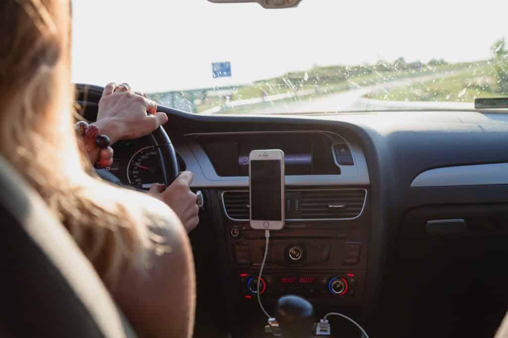 Imagem focada em painel de carro com celular desligado e moça dirigindo em estrada.