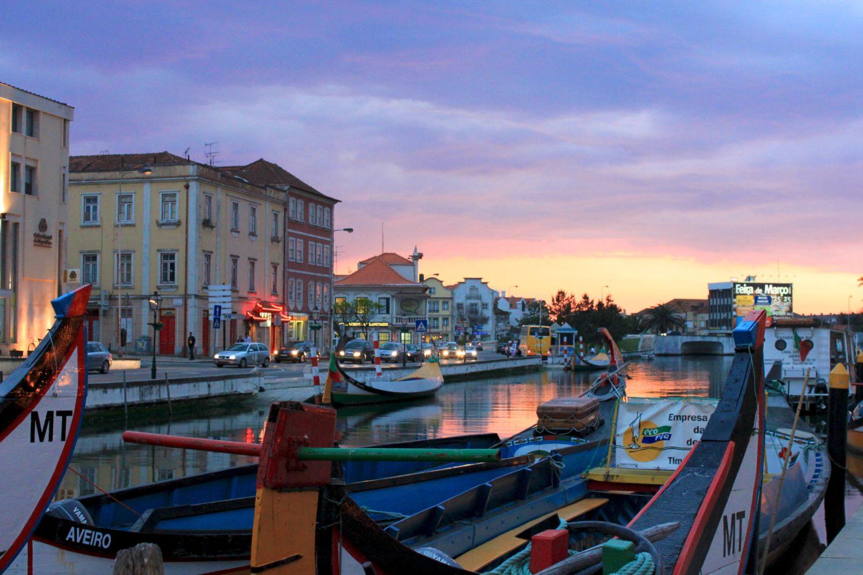 Entardecer na cidade de Aveiro, com prédios próximos ao rio navegado por barcos. Foto de Nmmacedo via Wikimedia.
