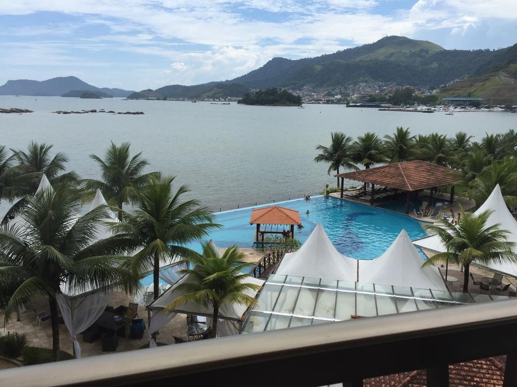 Vista da praia e piscina no Apartamento Charme e Comforto - Pousadas em Angra dos REis
