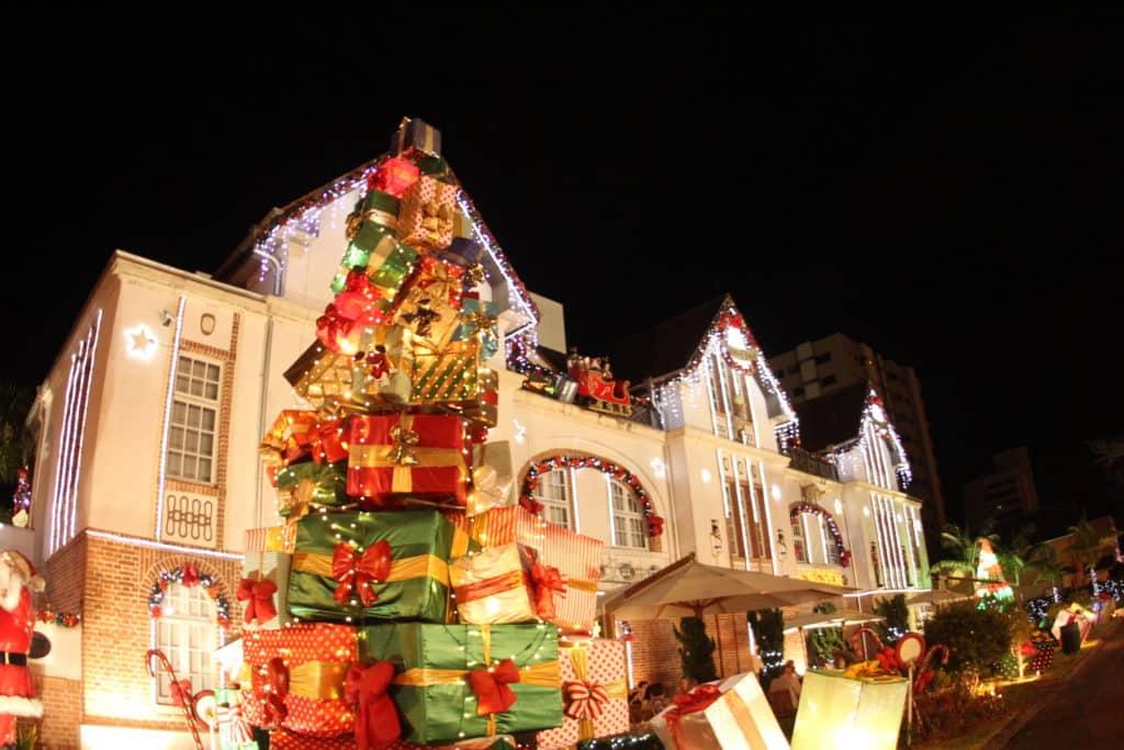 Na foto vemos a decoração de Natal da Vila Germânica Blumenau, com árvore montada de presentes e luzes típicas. Foto do site oficial Parque Vila Germânica.