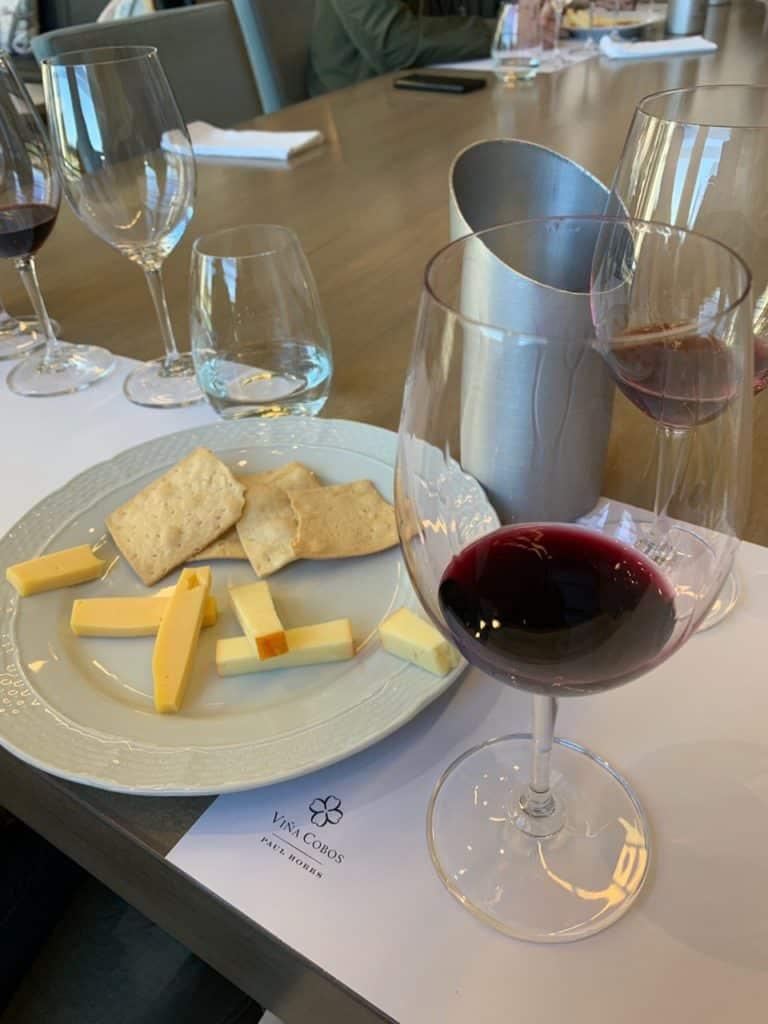 Taça de vinho da degustação na Vina Cobos com queijos e bolachas. Foto: Bruno Tavares