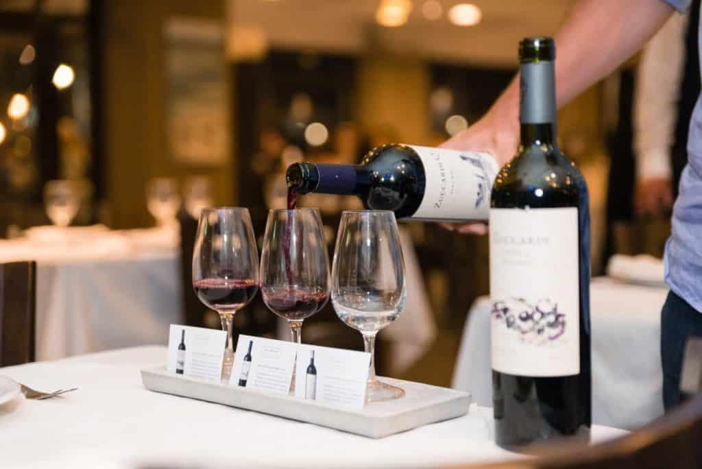 Na imagem vemos três taças postas em uma pequena bandeja, com plaquinhas indicativas de vinho à frente. A taça do meio está sendo serviça com vinho ZuccardiQ. Ao lado há outra garrafa de vinho Zuccardi. Foto da página da bodega no Facebook. Vinicola Mendoza
