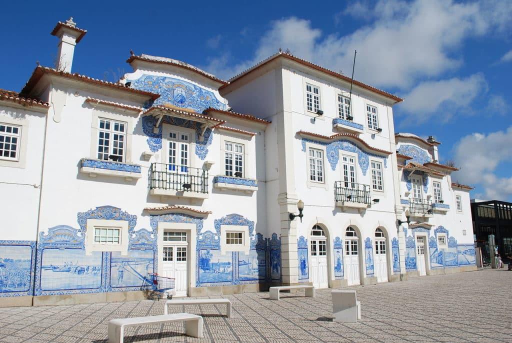 Vista da fachada da antiga estação ferroviária de Aveiro, com painéis de azulejos azuis típicos portugueses. Foto de Concierge.2C via Wikimedia.