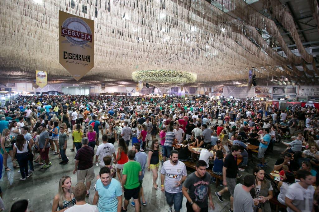 Vista de público do Festival Brasileiro da Cerveja, em galpão do Parque Vila Germânica. No teto existem bandeiras da cerveja EisenBahn e fitinhas decotativas. Foto do site oficial Parque Vila Germânica.