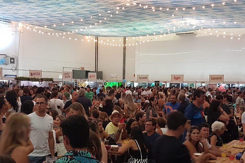 Área comum do Festival de Botecos de Blumenau, com bastante público, mesinhas com pessoas sentadas e barraquinhas ao fundo.
