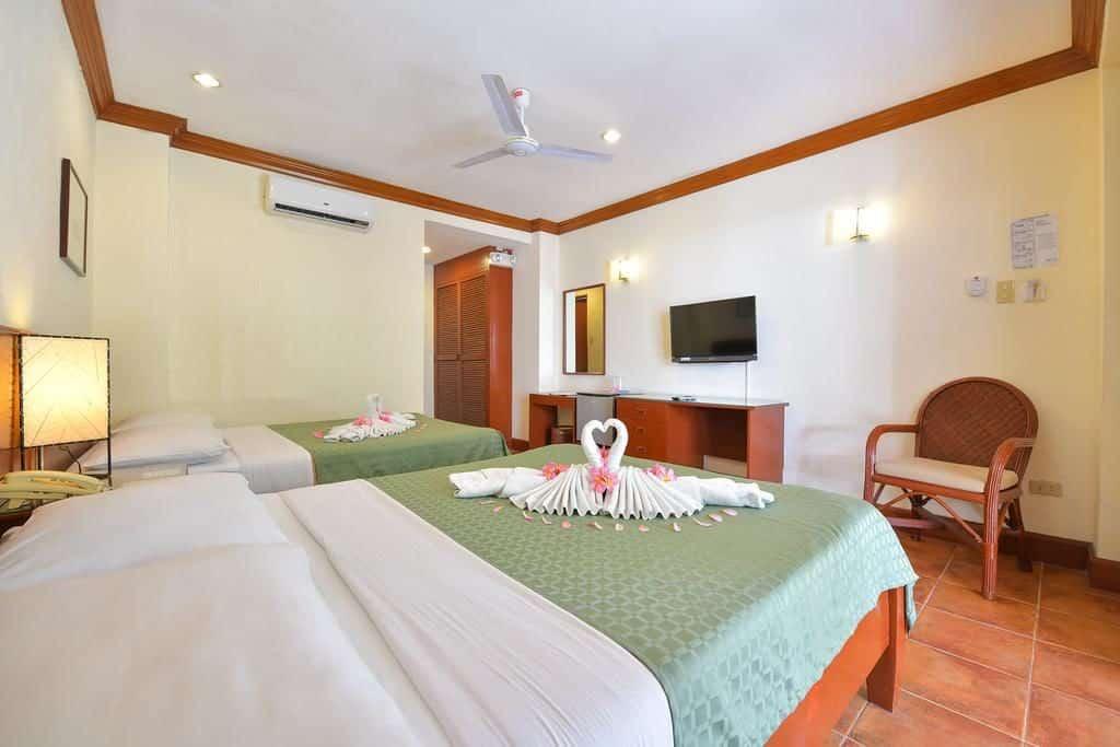 Opção barata de viagem pelo mundo é o Hey Judge - quarto com duas camas de solteiro com edredon verde