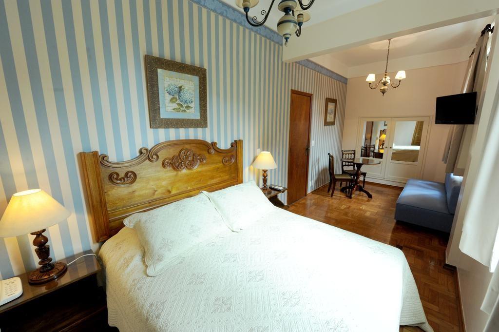 quarto de casal no hotel york com cama clara e papel de parede listrado