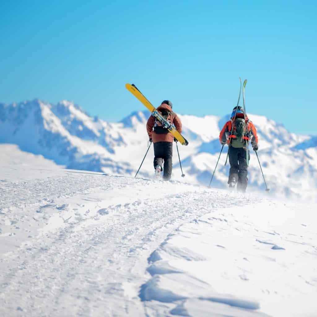 Imagem de caminho nevado nas montanhas, na estação de esqui Las Leñas, na Argentina. Há dois indivíduos na foto, ambos carregando equipamentos de esqui. Foto do instagram @laslenasresort
