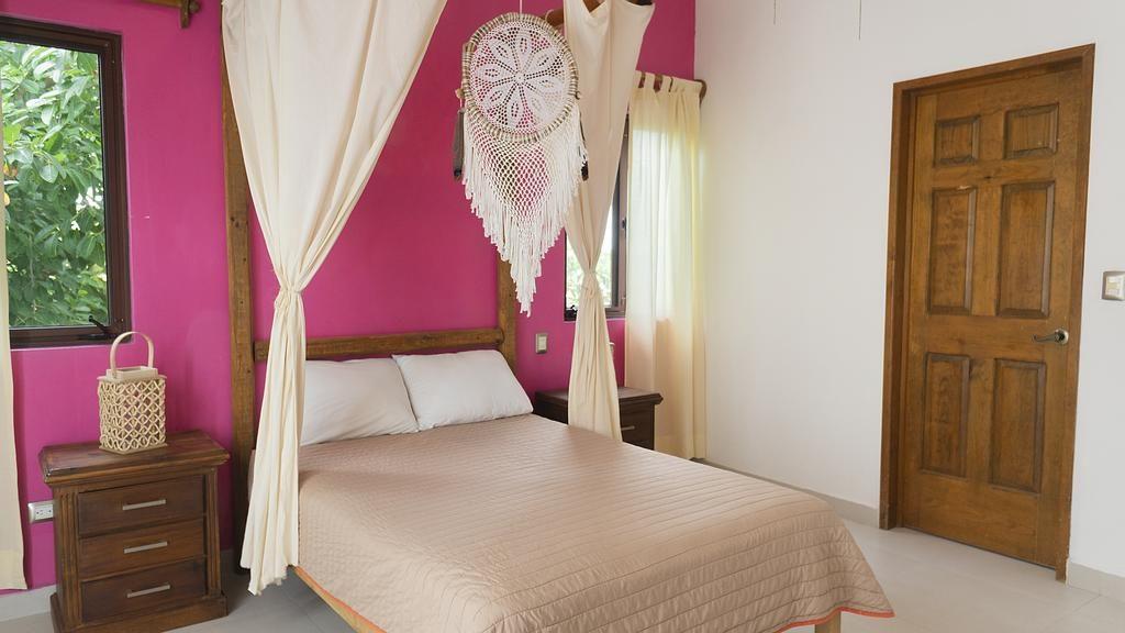 Quarto com colcha rosa no Mezcal Hotel Hostel & Bar - viajando barato pelo mundo