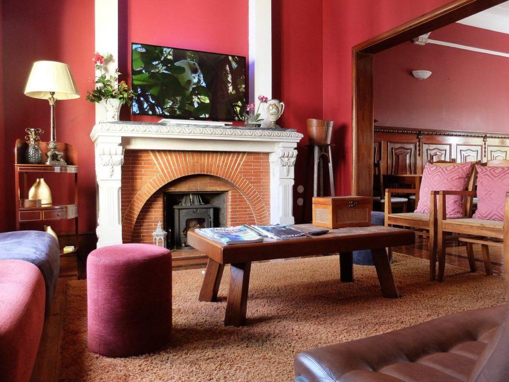 Sala de paredes vermelhas e lareira no Oc Salon, hospedagem em Aveiro Portugal. Foto de booking.com