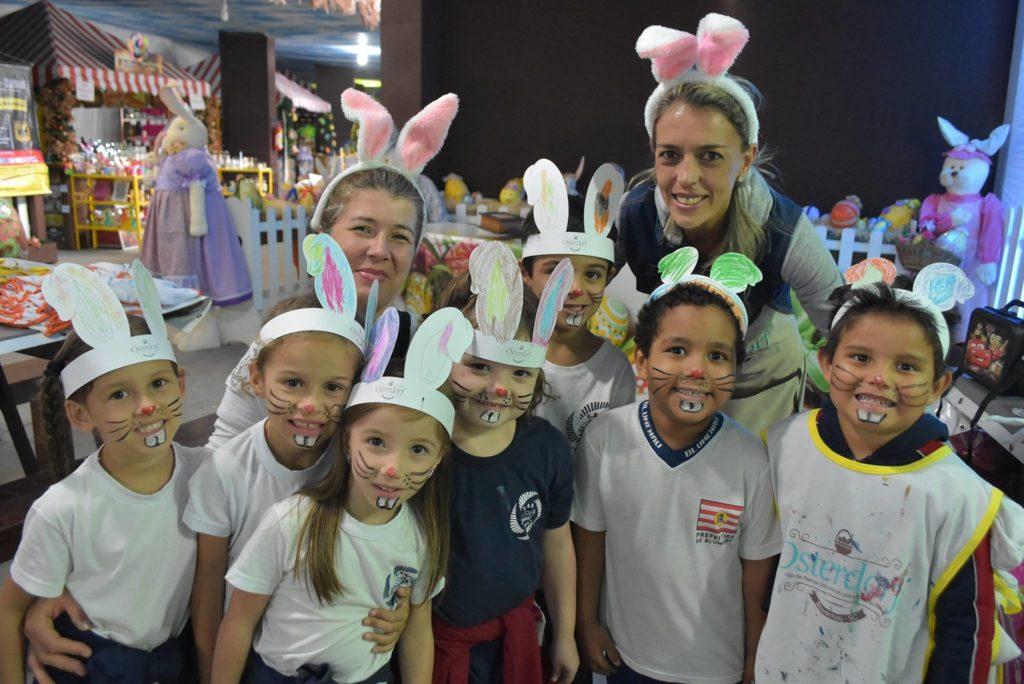 Na foto vemos 7 crianças com rostos pintados com nariz vermelho, bigode e dentinhos, usando orelhinhas de coelho feitas de papel, e duas mulheres adultas com orelhas de coelho de pelúcia. Foto facebook Vila Germânica.