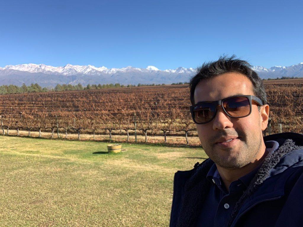 Na imagem vemos o colunista Bruno Tavares à frente dos vinhedos secos com as cores do Outono na bodega Andeluna. Ao fundo a Cordilheira dos Andes. Foto do Bruno Tavares.