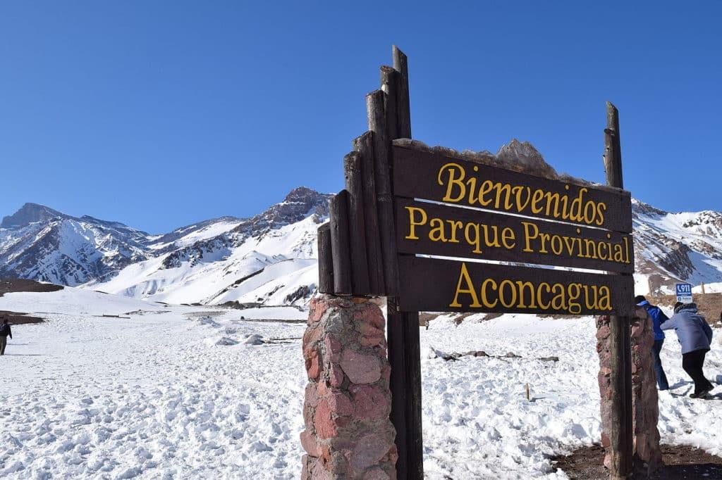 Placa de Bienvenidos no Parque Provincial do Aconcágua, com paisagem repleta de neve e montanhas ao fundo. Foto de Leandro Kibisz via Wikimedia.