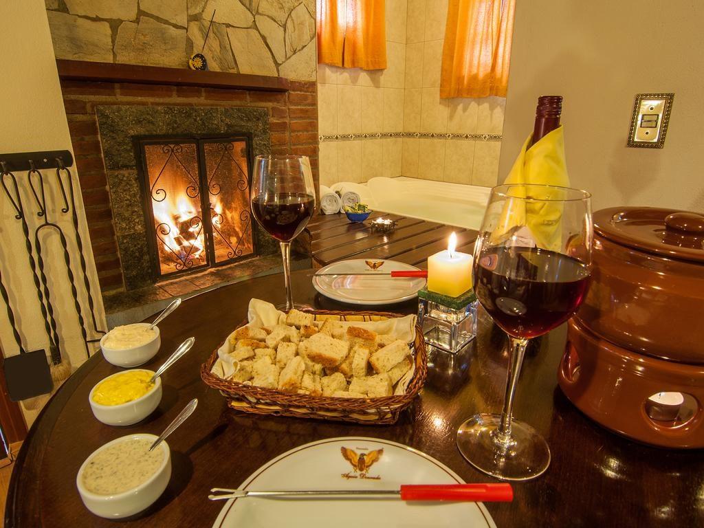 mesa de fondue com lareira ao fundo na pousada águia dourada em Monte Verde