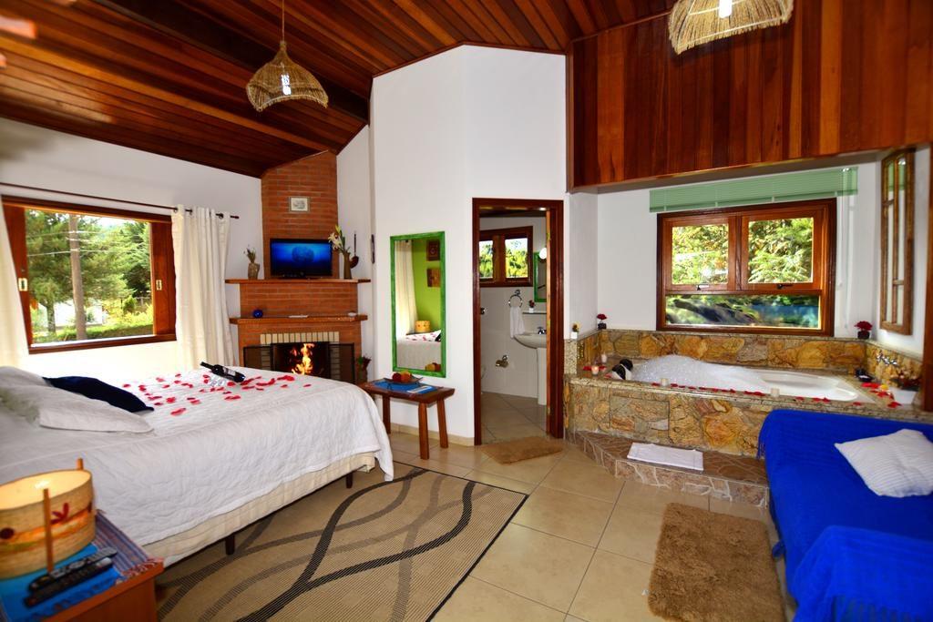 Quarto da Pousada Cantinho de Monte Verde com cama de Casal, vinho, lareira e banheira