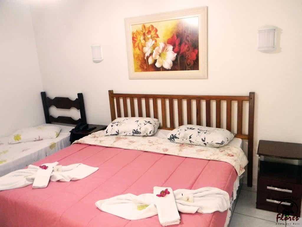 Quarto de casal com colcha rosa e toalhas na Pousada das Flores em Angra dos Reis RJ