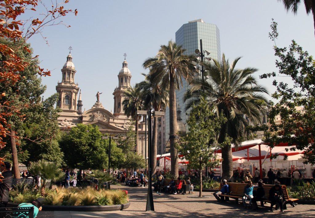 Vista de praça arborizada em Santiago do Chile, com igreja e prédio espelhado ao fundo. Foto: Moniza Volpin via Pixabay.