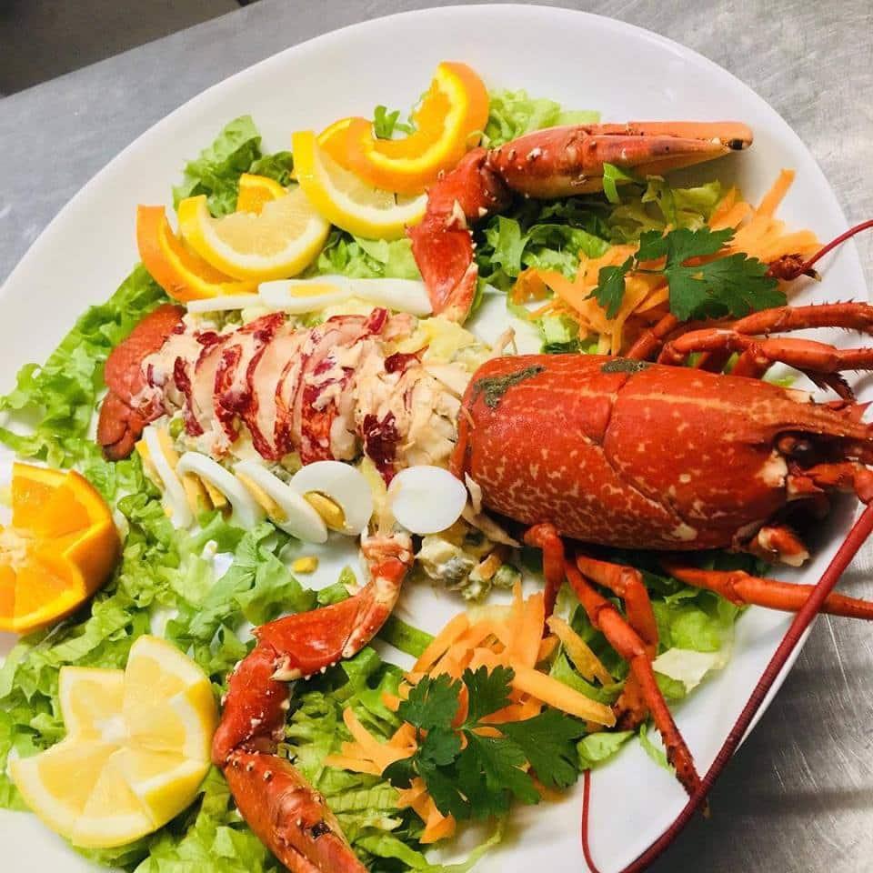 Vista de prato com lagosta, ovos, laranjas e salada de alface, cenoura e salsinha, do restaurante Maré Cheia. Foto da página do restaurante no Facebook.