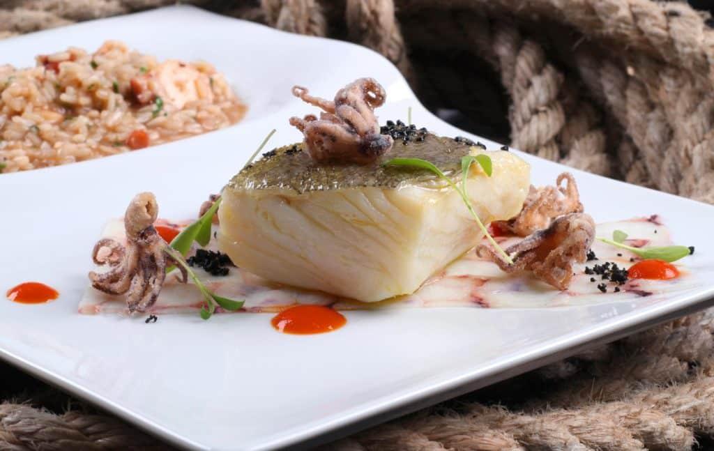 Imagem de prato de filé de peixe com mini polvos e guarnição de arroz, do restaurante SalPoente. Foto do site oficial do restaurante.