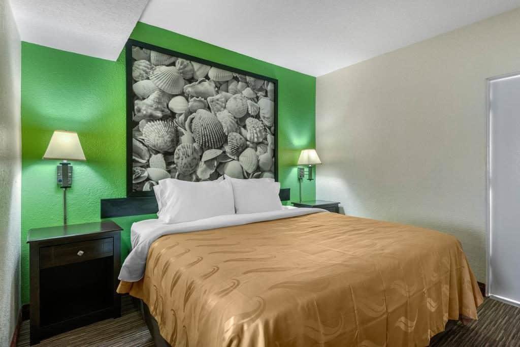 quarto do quality inn daytona beach, cama de casal com edredon amarelo e parede verde com quadro branco e preto - viajando barato pelo mundo