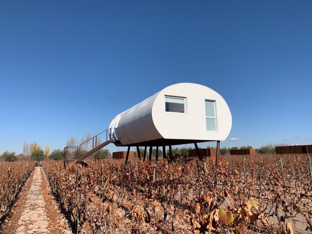 Na imagem vemos o quarto suspenso em formato de capsula branca, sobre os vinhedos secos por conta do Outono no Entre Cielos Mendoza. Foto: Bruno Tavares